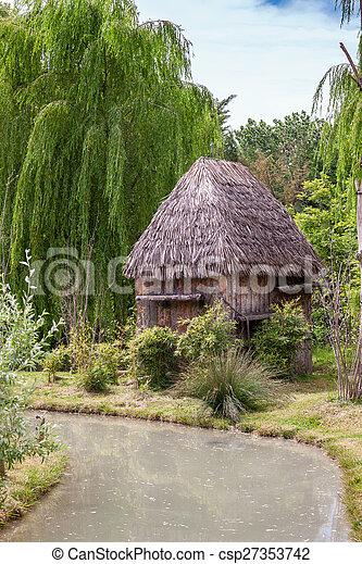 Una choza pequeña con techo de paja. - csp27353742