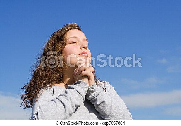 christian child praying a prayer outdoors at bible camp - csp7057864