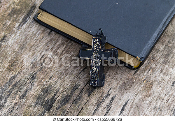 Christian Cross and Holy Bible on old wooden table - csp55666726