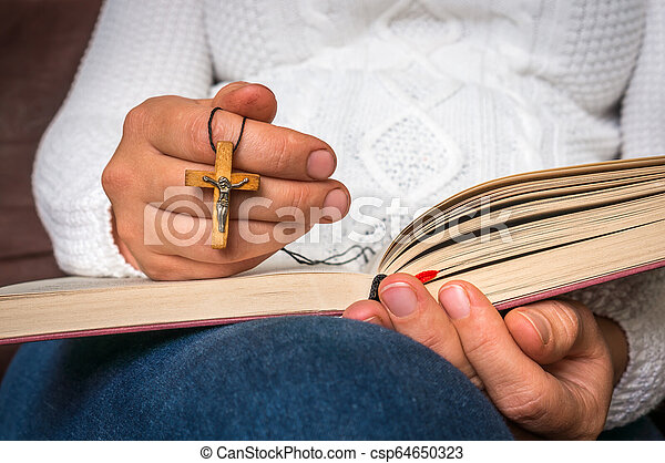 Christian woman with wooden cross reading a holy Bible - csp64650323