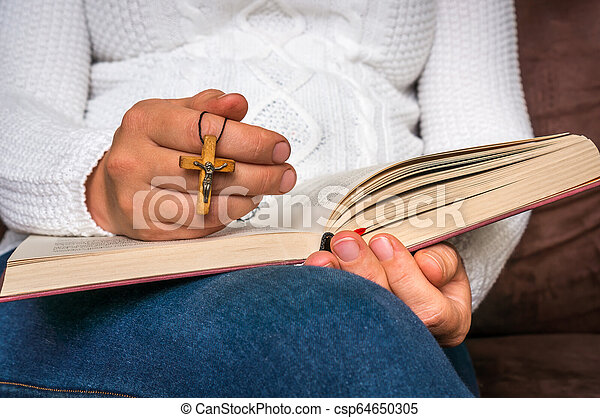Christian woman with wooden cross reading a holy Bible - csp64650305
