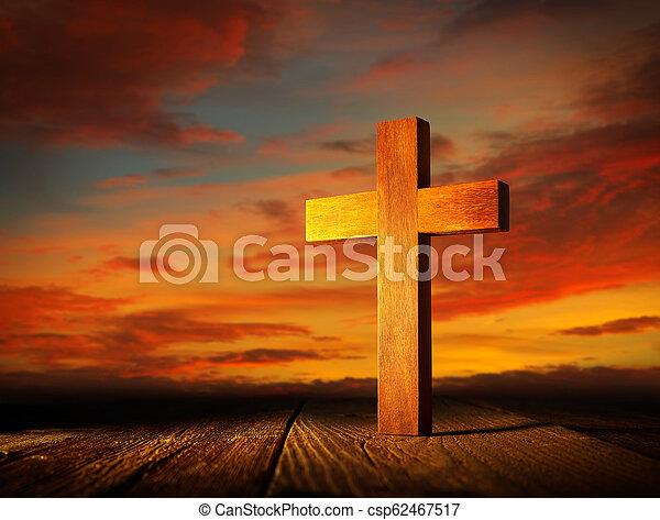 Christian wood cross on sunset sky - csp62467517