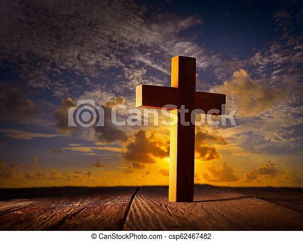 Christian wood cross on sunset sky - csp62467482