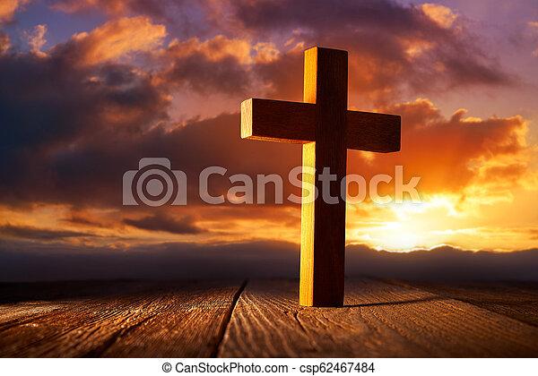 Christian wood cross on sunset sky - csp62467484