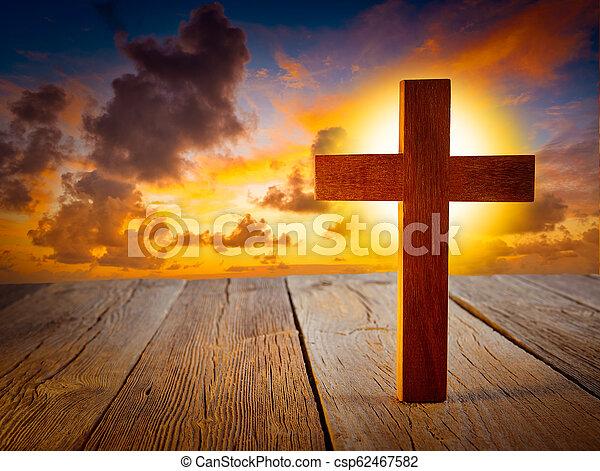 Christian wood cross on sunset sky - csp62467582