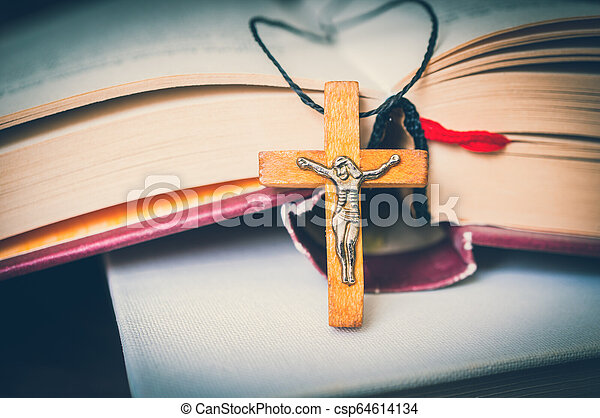 Christian wooden cross necklace on holy Bible - csp64614134