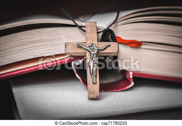 Christian wooden cross necklace on holy Bible - csp71780233