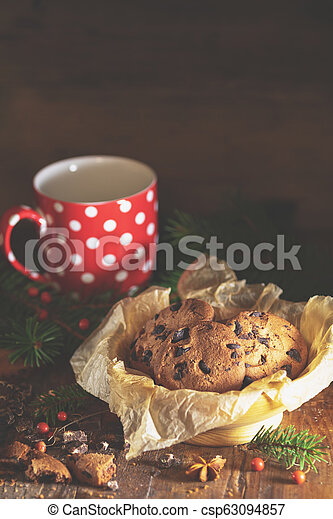 Christmas and New Year composition with delicious chocolate cookies, peanuts and cup of coffee or tea, spruce branches and pine cones - csp63094857