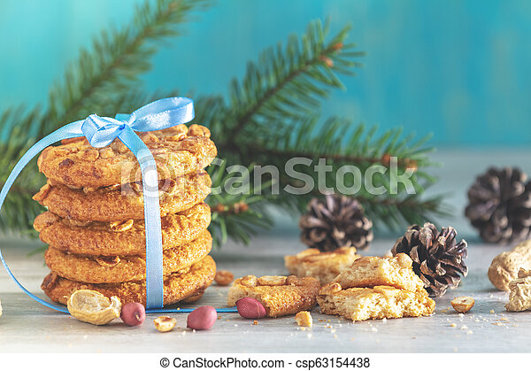 Christmas and New Year composition with delicious peanut cookies, peanuts, spruce branches and pine cones - csp63154438