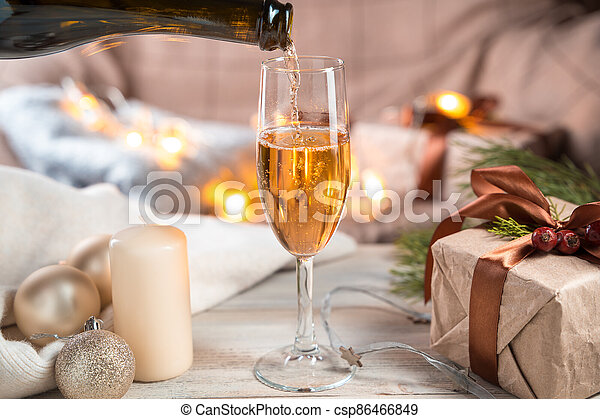 Christmas background with a bottle filling a glass of champagne on a light background. - csp86466849