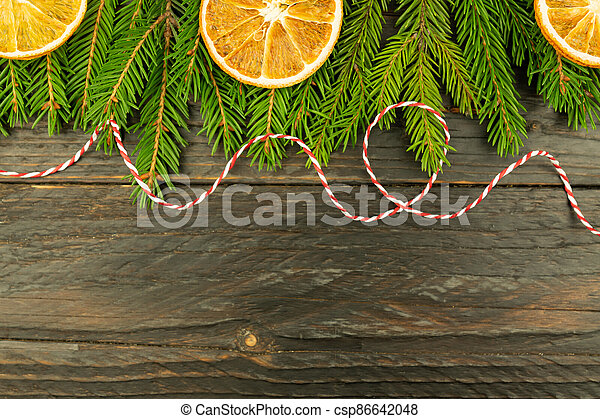 Christmas background with fur-tree branches, dried oranges on wooden background. - csp86642048