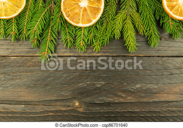 Christmas background with fur-tree branches, dried oranges on wooden background. - csp86701640