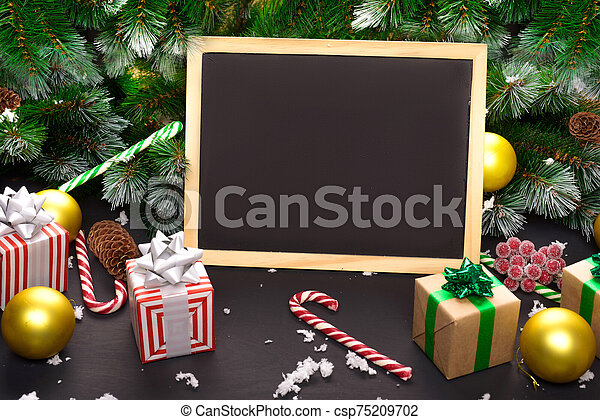 Christmas Board, gift box, Christmas tree branch, Christmas decorations on wooden dark background. Top view with copy space for your text. - csp75209702