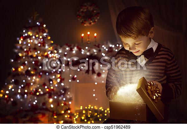 christmas child open present gift box happy kid opening giftbox in xmas tree home interior