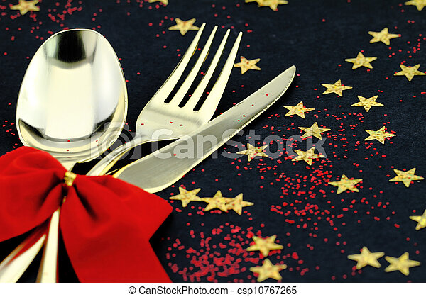Christmas cutlery. Spoon, fork and knife stacked up on a starry background - csp10767265