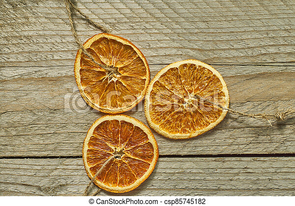 Christmas decor. dried orange slices for new year tree decoration on wooden background - csp85745182
