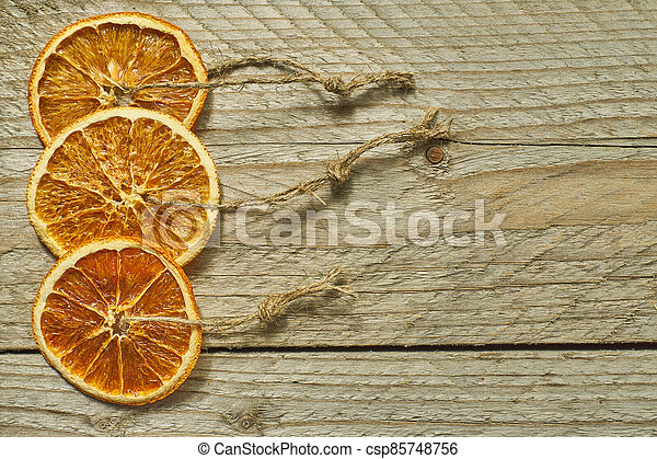 Christmas decor. dried orange slices for new year tree decoration on wooden background - csp85748756
