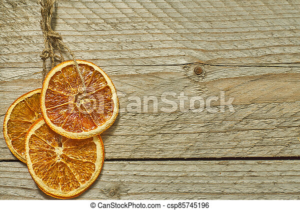 Christmas decor. dried orange slices for new year tree decoration on wooden background, copy space for your text - csp85745196