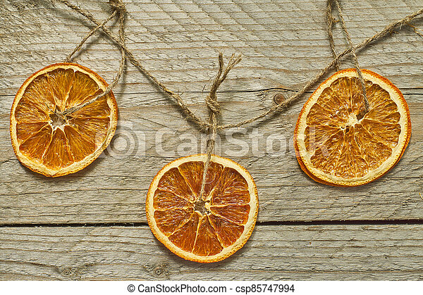 Christmas decor. dried orange slices for new year tree decoration on wooden background - csp85747994