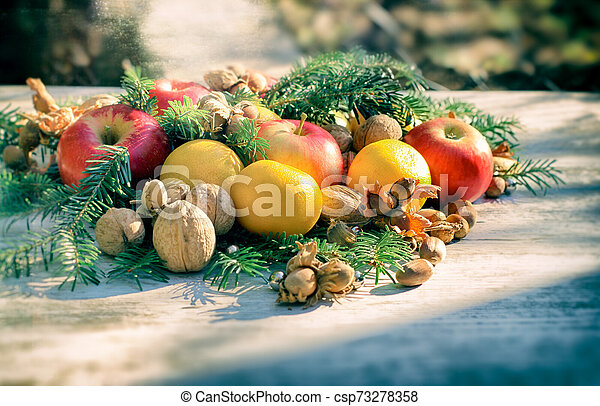 Christmas decoration with organic fruit on table for upcoming holidays - csp73278358