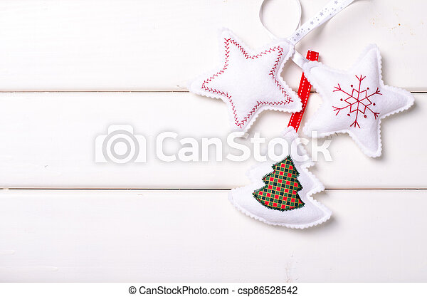 Christmas decorations with stars and tree on white wooden background. Xmas and Happy New Year composition - csp86528542