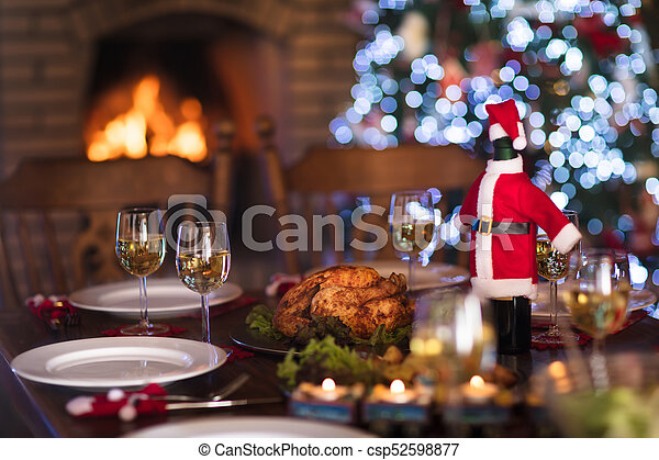christmas dinner at fire place and xmas tree csp52598877
