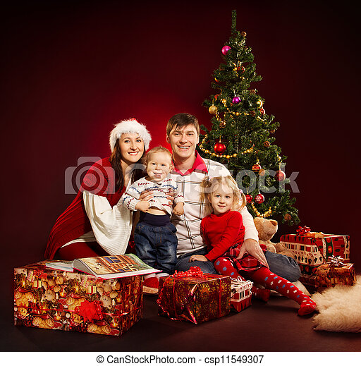 Christmas family of four persons and fir tree with gift boxes csp11549307