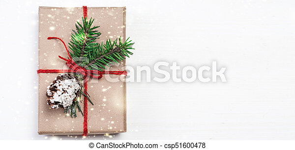 Christmas gift box with xmas decorations as greeting card. Festive boxes of Christmas present with ribbon bow and fir tree branch on white background - csp51600478