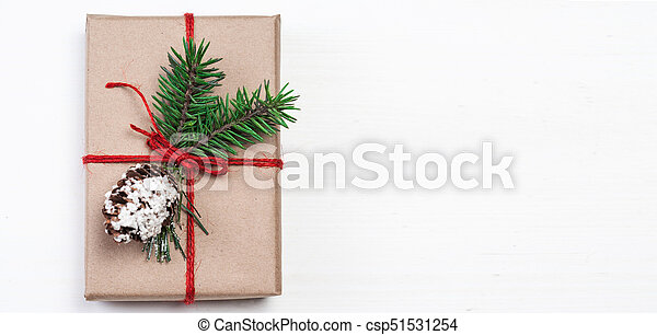 Christmas gift box with xmas decorations as greeting card. Festive boxes of Christmas present with ribbon bow and fir tree branch on white background - csp51531254