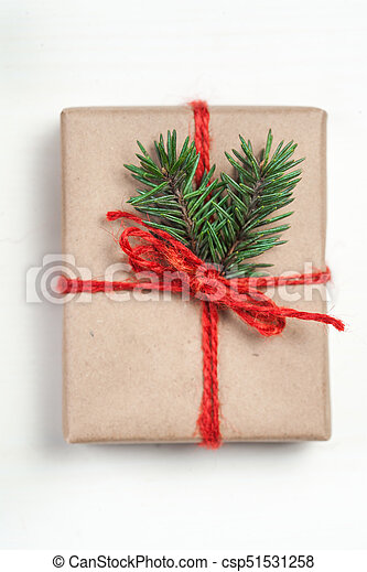 Christmas gift box with xmas decorations as greeting card. Festive boxes of Christmas present with ribbon bow and fir tree branch on white background - csp51531258