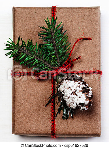 Christmas gift box with xmas decorations as greeting card. Festive boxes of Christmas present with ribbon bow and fir tree branch on white background - csp51627528