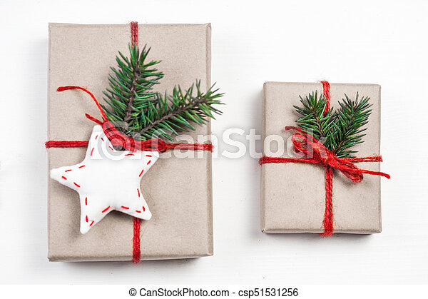 Christmas gift boxes with xmas decorations. Greeting card wiyh Christmas present, red ribbon bow and fir tree branch on white background. Craft paper package - csp51531256