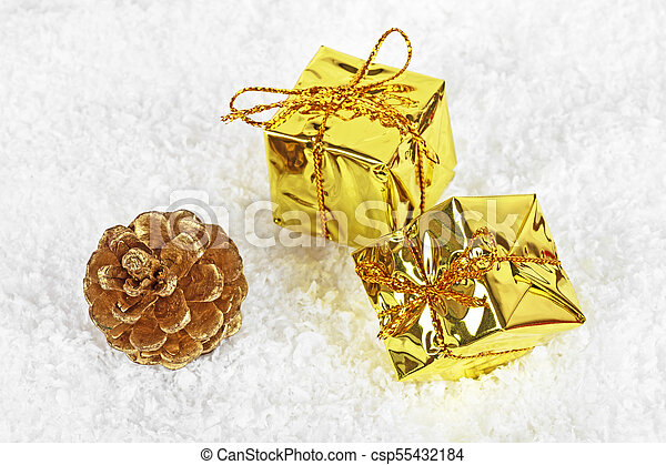 Christmas gold boxes and golden pine cone in the snow - csp55432184
