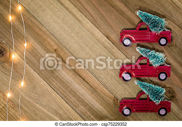 Christmas Holiday Winter still life concept on wooden board with vintage red truck and tree decor, flat lay room for text copy - csp75229352