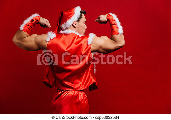 61889e4251b94 Christmas Holidays. Sexy Strong Santa Claus Wearing Hat. Young Muscular Man.  Red Background.