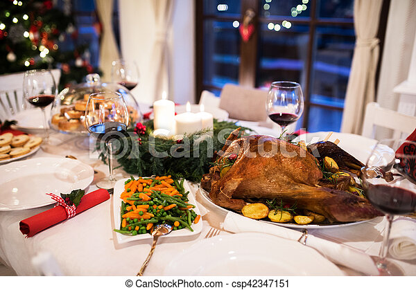 Christmas meal laid on table in decorated dining room. - csp42347151