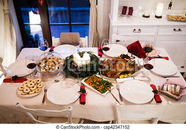 Christmas meal laid on table in decorated dining room. - csp42347152