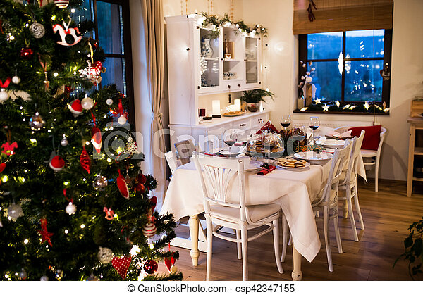 Christmas meal laid on table in decorated dining room. - csp42347155