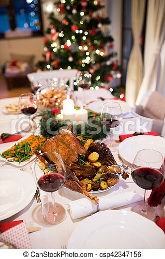 Christmas meal laid on table in decorated dining room. - csp42347156
