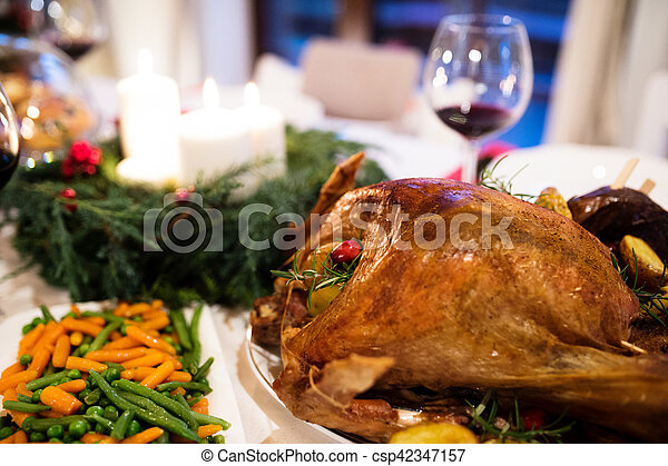 Christmas meal laid on table in decorated dining room. - csp42347157