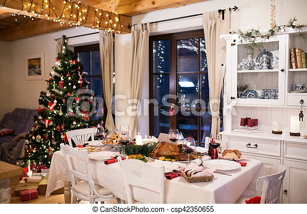 Christmas meal laid on table in decorated dining room. - csp42350655