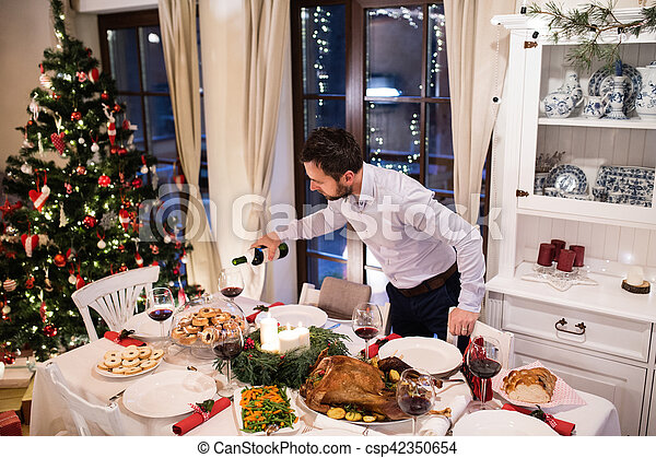 Christmas meal laid on table. Man pouring wine into glasses. - csp42350654