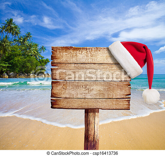 Christmas on beach. Wooden signboard with Santa's hat. - csp16413736