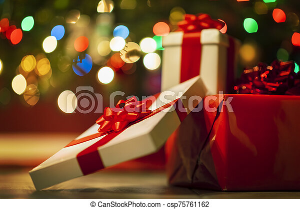 Christmas presents with christmas tree lights on background - csp75761162