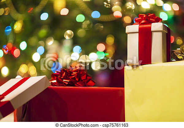 Christmas presents with christmas tree lights on background - csp75761163