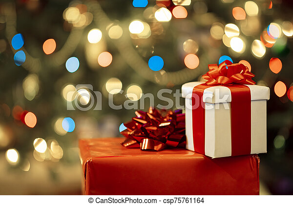 Christmas presents with christmas tree lights on background - csp75761164