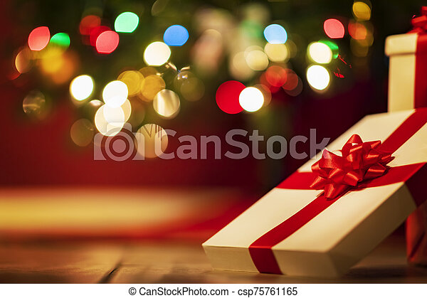 Christmas presents with christmas tree lights on background - csp75761165