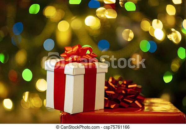 Christmas presents with christmas tree lights on background - csp75761166
