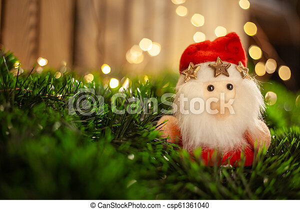 Christmas toy Santa Claus in green tinsel against the background of a garland - csp61361040