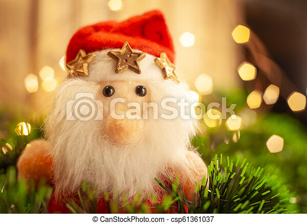Christmas toy Santa Claus in green tinsel against the background of a garland - csp61361037